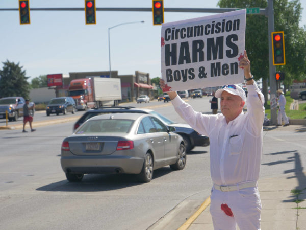 """A bloodstained man holds a sign above his head – """"Circumcision Harms Boys and Men"""""""