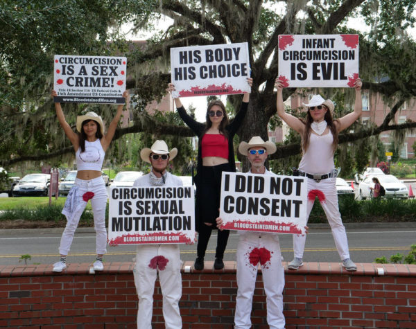 """Five protesters hold signs reading """"Circumcision is Sexual Mutilation"""", """"I Did Not Consent"""", """"Circumcision is a Sex Crime"""", """"His Body His Choice"""", and """"Infant Circumcision is Evil""""."""