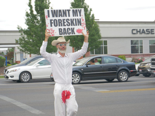 """A bloodstained man holds a sign above his head – """"I Want My Foreskin Back"""""""