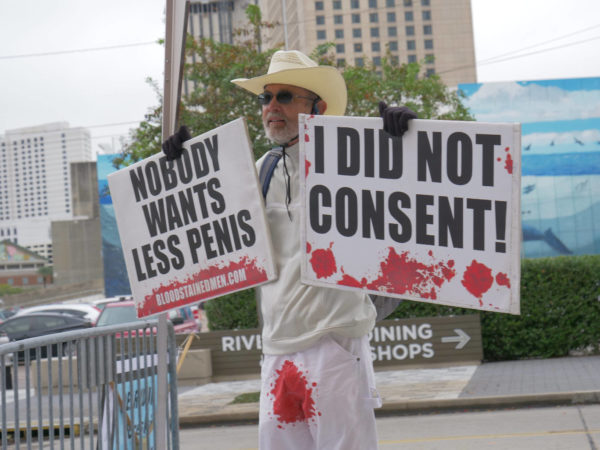"""A bloodstained man holds two signs – """"Nobody Wants Less Penis"""" and """"I Did Not Consent"""""""
