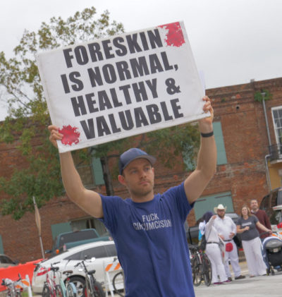 """A man holds a sign reading """"Foreskin is Normal, Healthy, and Valuable"""""""