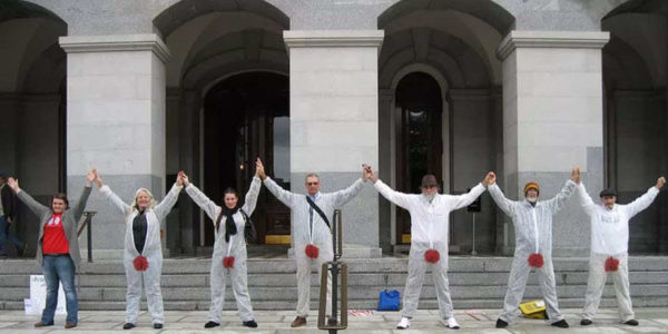 Six protesters in bloodstained suits oppose the genital mutilation of baby boys