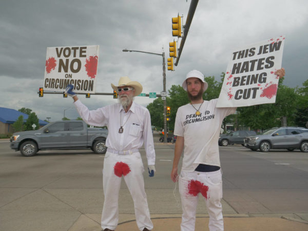 "Two bloodstained men in Colorado hold protest signs – ""Vote No on Circumcision"" and ""This Jew Hates Being Cut"""