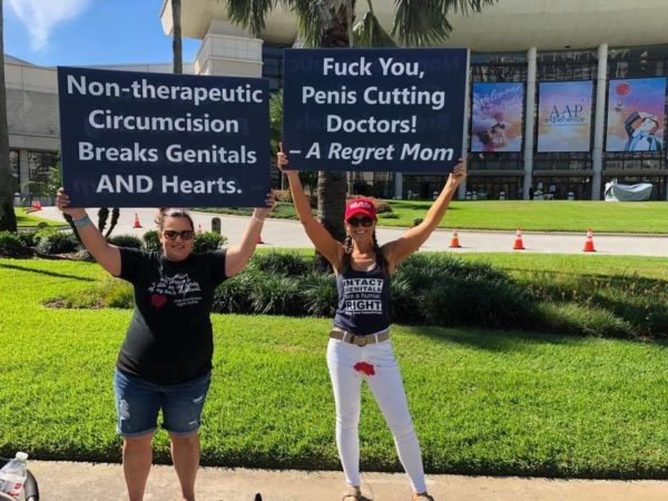 """Two women hold signs reading """"Fuck You, Penis Cutting Doctors! - A Regret Mom"""" and """"Non-therapeutic Circumcision Breaks Genitals and Hearts"""""""