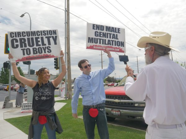 "Two protesters in street clothes with felt bloodstains pinned to their crotches hold signs reading ""Circumcision Cruelty to Boys"" and ""End Male Genital Mutilation"""